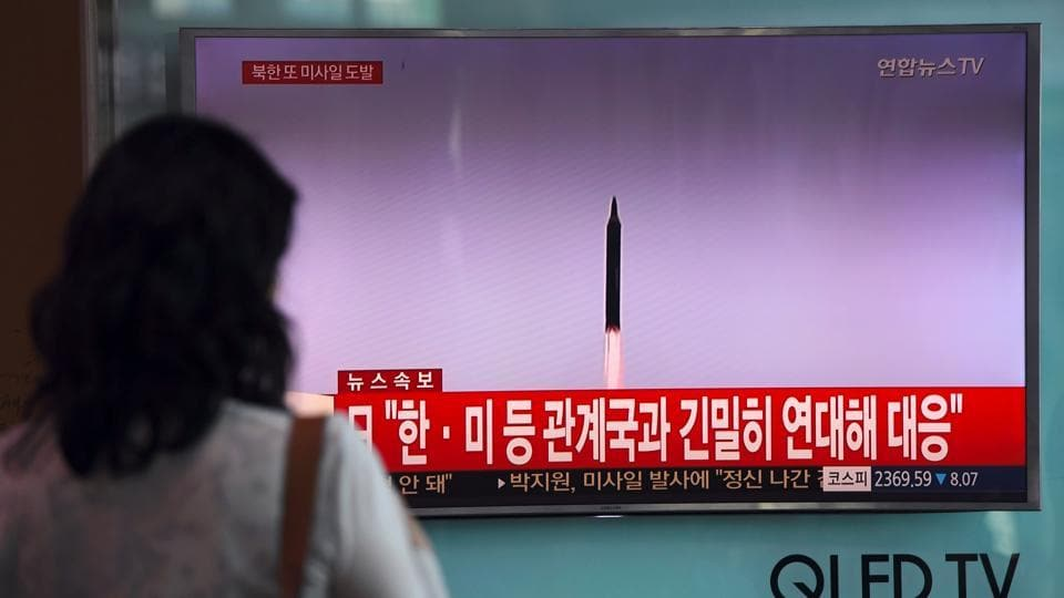 A woman watches a screen showing file footage of a North Korean missile launch. North Korea this week fired its second missile over Japan in less than a month and threatened to sink the country into the sea with nuclear weapons.