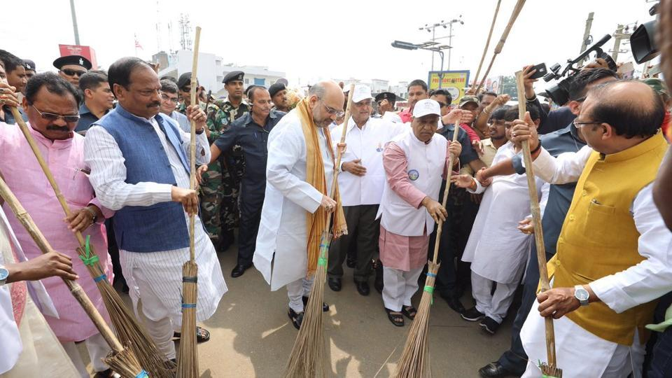 BJP president Amit Shah sweeps the street promoting Prime Minister Narendra Modi's Swachh Bharat Abhiyan.