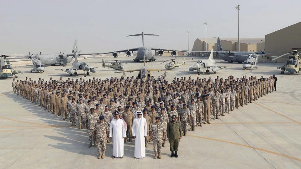 In a September released photo by the Qatar News Agency, the Qatari Emir Sheikh Tamim bin Hamad Al Thani (centre front) poses for a photo with Emiri Air Force at al-Udeid Air Base in Doha, Qatar.