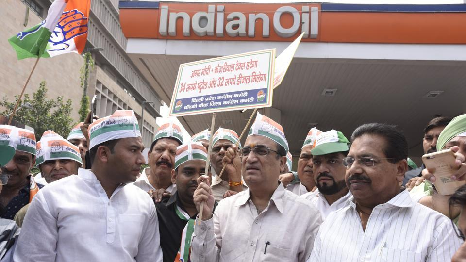 Delhi Congress chief Ajay Maken with party workers at a petrol pump during a signature campaign to protest against fuel price hike, in New Delhi.