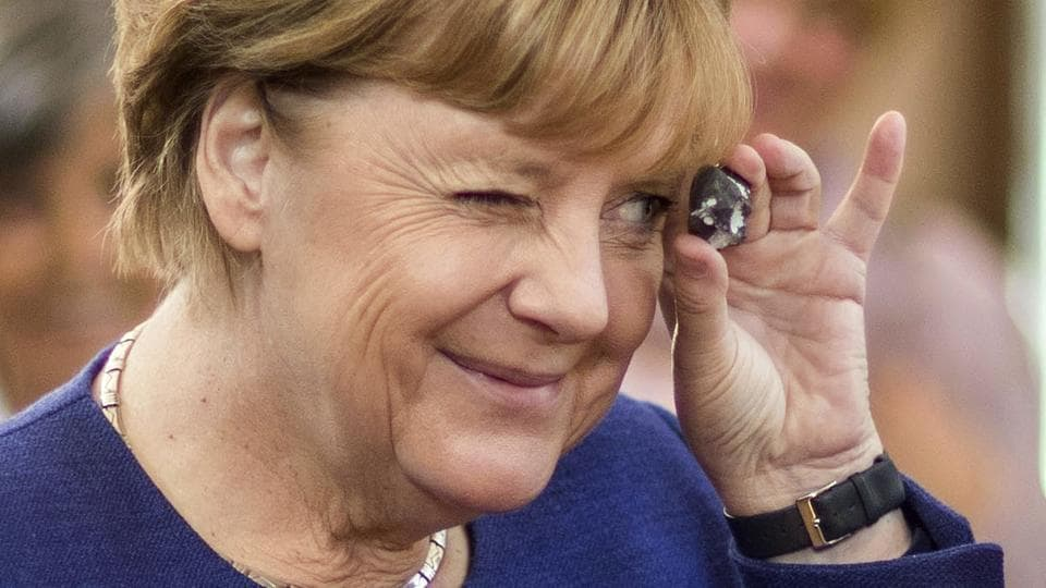 German Chancellor Angela Merkel peeks through a souvenir gifted by a visitor during an election campaign in Vilmnitz, northern Germany, on September 16, 2017.