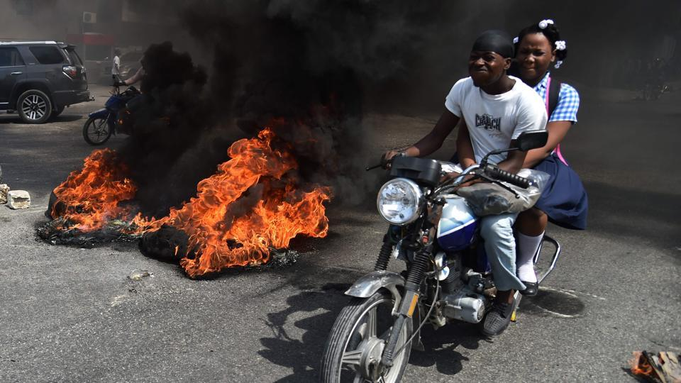 A couple on a motorcycle drive past burning tires placed by demonstrators on a main road in the Haitian capital Port-au-Prince, on September 12, 2017. Demonstrators took to the streets to protest against the government and the new budget for 2018, throwing stones at the police, setting tires on fire and blocking some streets. (Hector Retamal / AFP)