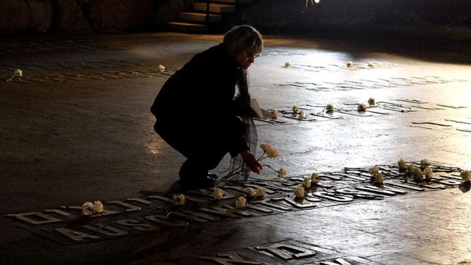 A woman places a flower at the Hall of Remembrance where the names of major killing sites of Jews are written during a Holocaust Remembrance Day ceremony at the Yad Vashem Holocaust Museum in Jerusalem.
