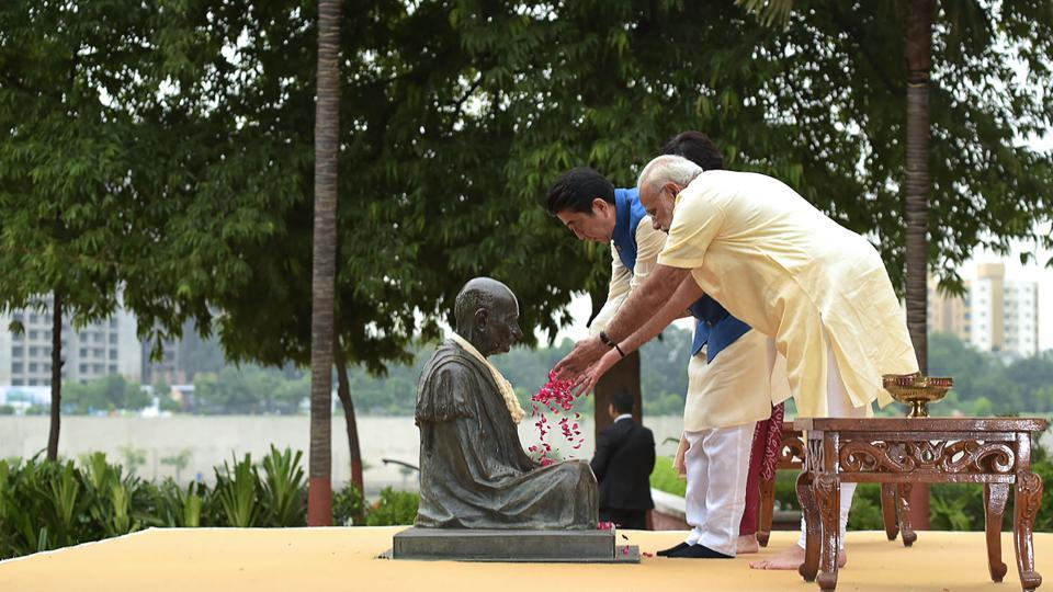 This handout photograph released by India's Press Information Bureau (PIB) on September 13, 2017, shows Prime Minister Narendra Modi (R), Japanese Prime Minister Shinzo Abe (L) and Abe's wife Akie (unseen) paying tribute to Mahatma Gandhi at Sabarmati Ashram, in Ahmedabad. (PIB / AFP)