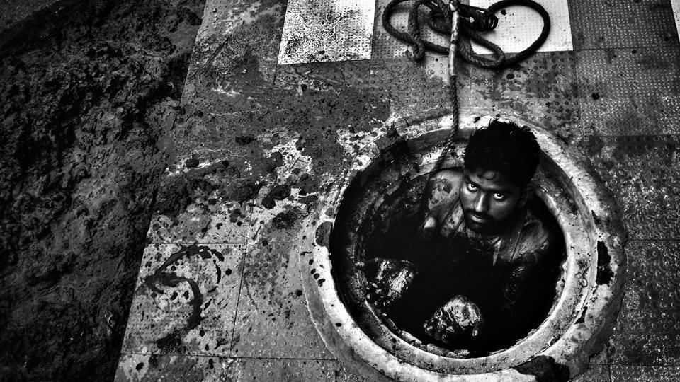 25-year-old Vikas, strips down and lowers himself into a sewer full of silt. Soon he is up to his chest in black muck. He fills a pail with the silt, which his co-workers pull out with the help of the rope attached to it, and empty it, before sending it back to him. The stench is overpowering, even for someone standing near.  (Ravi Choudhary / HT Photo)