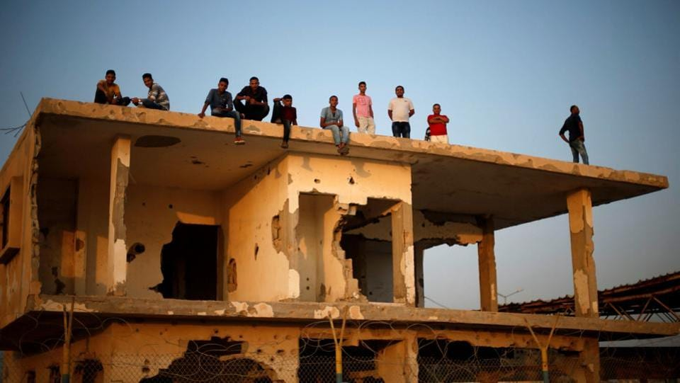 Palestinians gather atop a damaged building as they wait for the return of their relatives after performing the annual Haj pilgrimage in Mecca, at Rafah border crossing, in the southern Gaza Strip September 13, 2017.  (Mohammed Salem / Reuters)