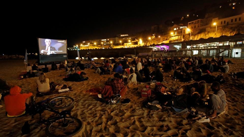 People watch a movie on a beach at night in Marseille, France, on September 13, 2017. A woman attacked four tourists with acid at a train station in Marseille, injuring two.
