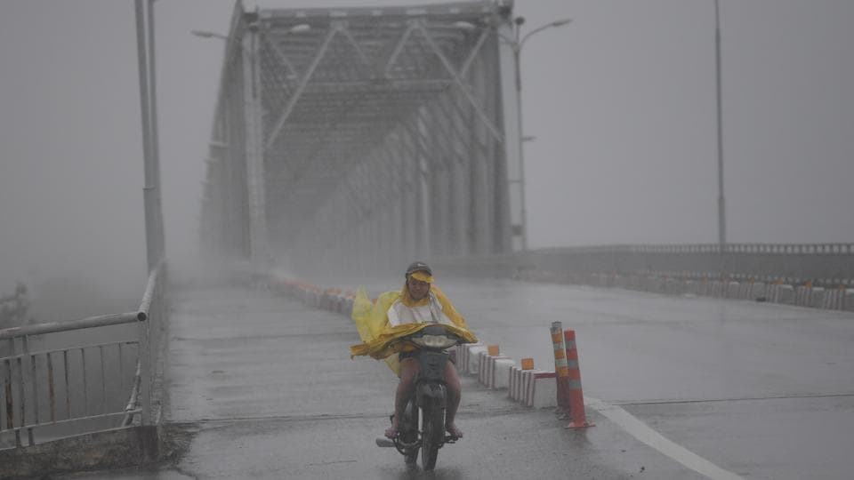 A woman rides a motorcycle across a bridge on a highway in the central province of Ha Tinh as Typhoon Doksuri makes landfall to the country's central coast on September 15, 2017. Heavy rain and wind lashed Vietnam's central coast Friday as Typhoon Doksuri made landfall, prompting mass evacuations as officials predicted it could be the most powerful storm in a decade. (Hoang Dinh Nam / AFP)
