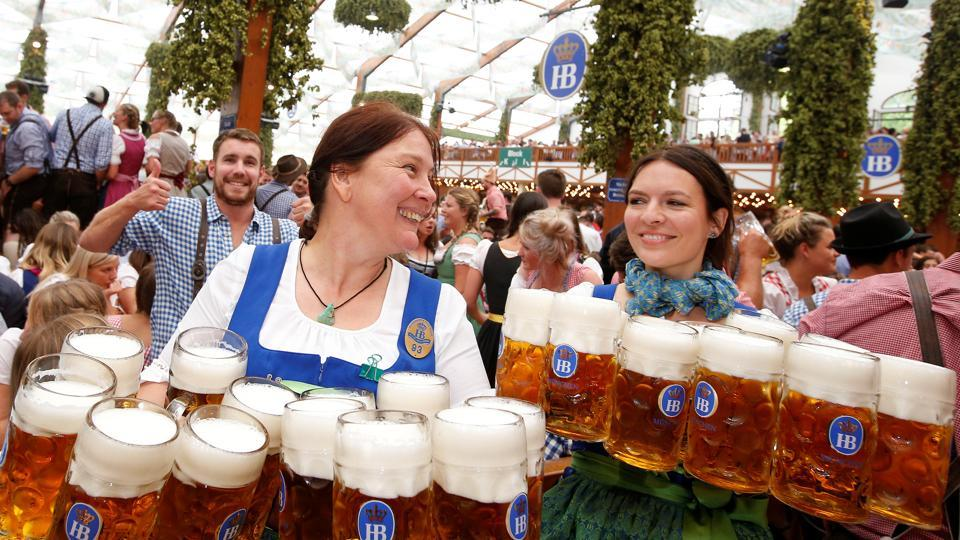 Waitresses carry mugs of beer during the opening day of the 184th Oktoberfest in Munich, Germany.