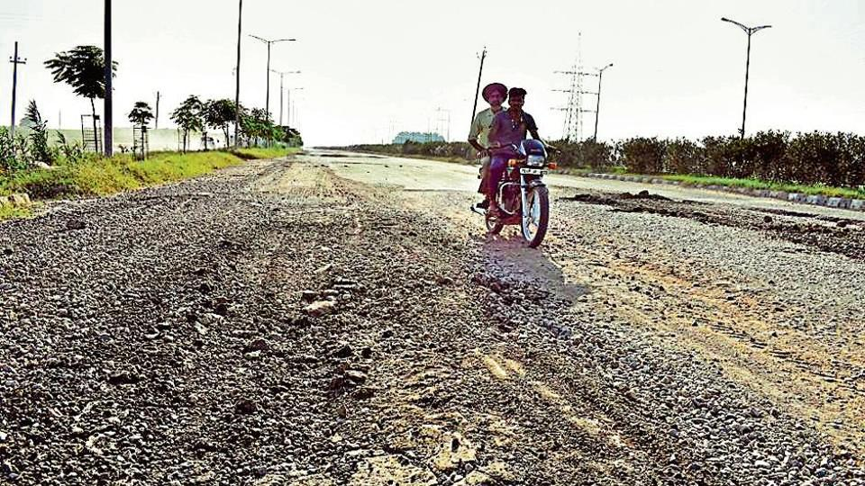 A biker negotiates Airport Road dotted with potholes.
