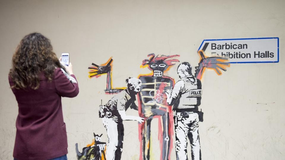 A woman takes a photo of one of two new murals painted by the artist Banksy near the Barbican Centre in central London.