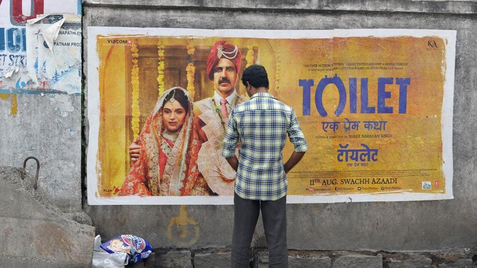 An Indian man urinates on a wall on the roadside in front of a poster for the Hindi film Toilet: Ek Prem Katha, August 11, 2017