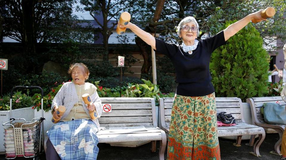 Natsu Naruse (L), 100 year-old, and other participants exercise with wooden dumbbells during a health promotion event.