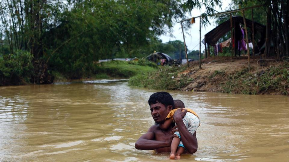 A Rohingya refugee carries a baby through a swollen stream in Cox's Bazar, Bangladesh, on September 18, 2017.