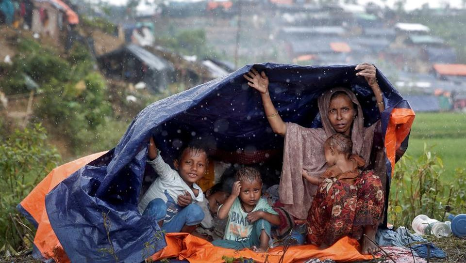 Rohingya refugees shelter from the rain in a camp in Cox's Bazar, Bangladesh, September 17, 2017. REUTERS/Cathal McNaughton