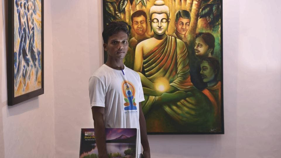 Ramesh, an inmate poses for a photo in front of his art work on display at a gallery at the Tihar School Of Art in New Delhi. The paintings are in different mediums—oil, acrylic, water paint—dealing with myriad themes of streetscapes, metro trains, portraits of women, the ghats of Banaras among many others. (Vipin Kumar / HT Photo)