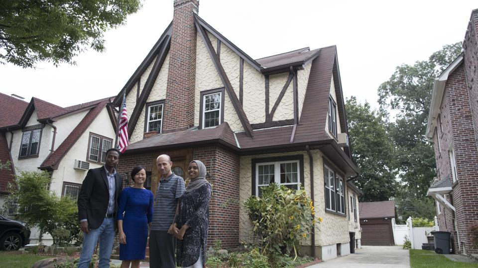 Abdi Iftin (L) of Somalia, Uyen Nguyen of Vietnam (2nd from L), Eiman Ali of Somalia (R0 and Ghassan al-Chahada of Syria pose for a photo outside US President Donald Trump's boyhood home in the Jamaica Estates neighbourhood of the Queens borough of New York.