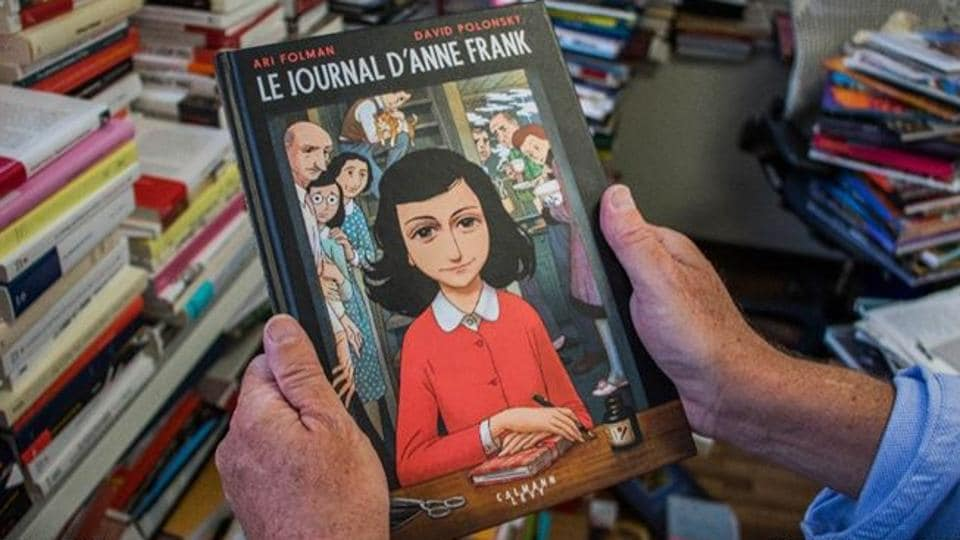 A man holds a copy of the graphic novel version of The Diary of Anne Frank, by Israeli writer-director Ari Folman and illustrator David Polonsky, in Paris on September 18, 2017.