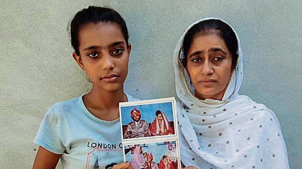 Balwinder Kaur showing her wedding photographs. Her husband Gurpiar Singh of Machhike village near Khemkaran left for the United Kingdom in 2003, never to return.