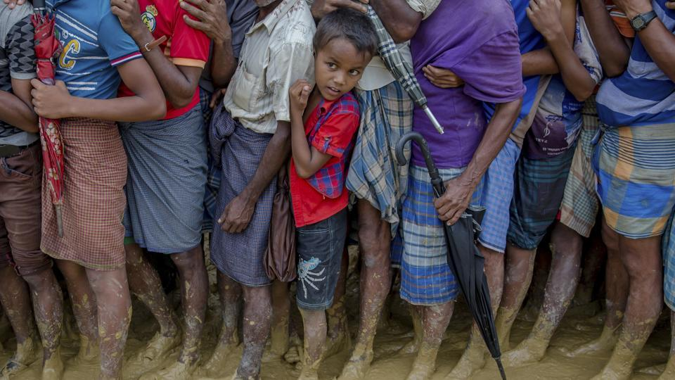 A young Rohingya Muslim boy, who crossed over from Myanmar into Bangladesh, waits along with others for his turn to collect food aid near Kutupalong refugee camp, Bangladesh, Tuesday.