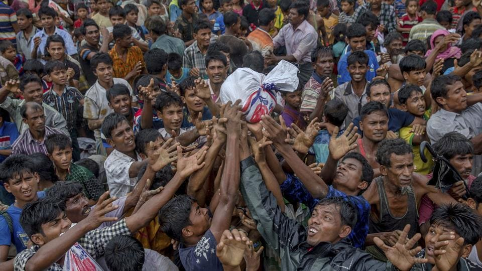 Rohingya Muslims stretch their arms out to collect food near Balukhali refugee camp, Bangladesh. Officials in the Northeast fear many refugees would try and infiltrate Assam. (AP Photo/Dar Yasin)