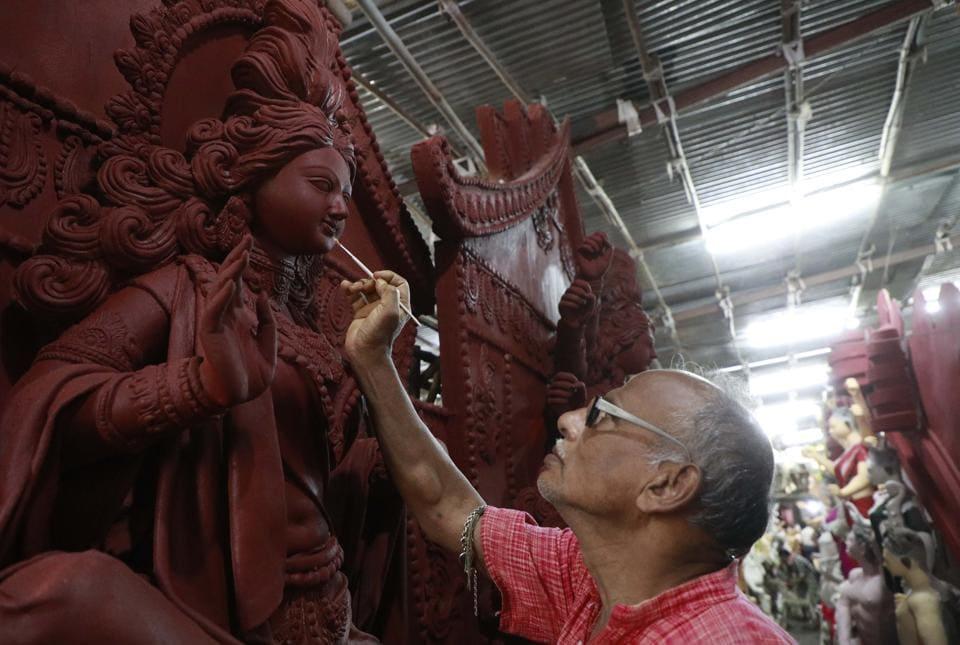 Shukharajan Pal works on one of his Durga idols at Khadki Kumartuli in Pune on Monday.