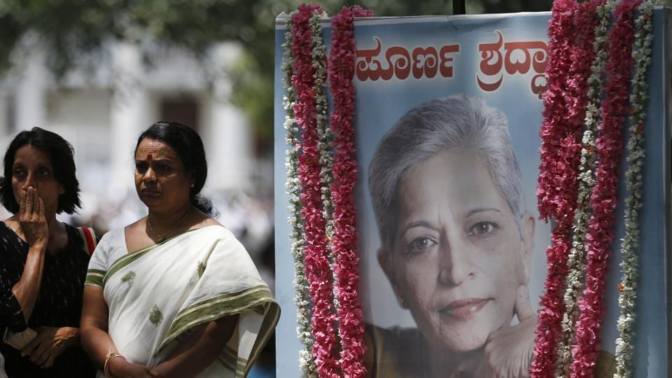 Mourners stand next to a portrait of journalist Gauri Lankesh in Bangalore on September 6. She was gunned down outside her home the southern city of Bangalore — the latest in a string of deadly attacks targeting journalists.