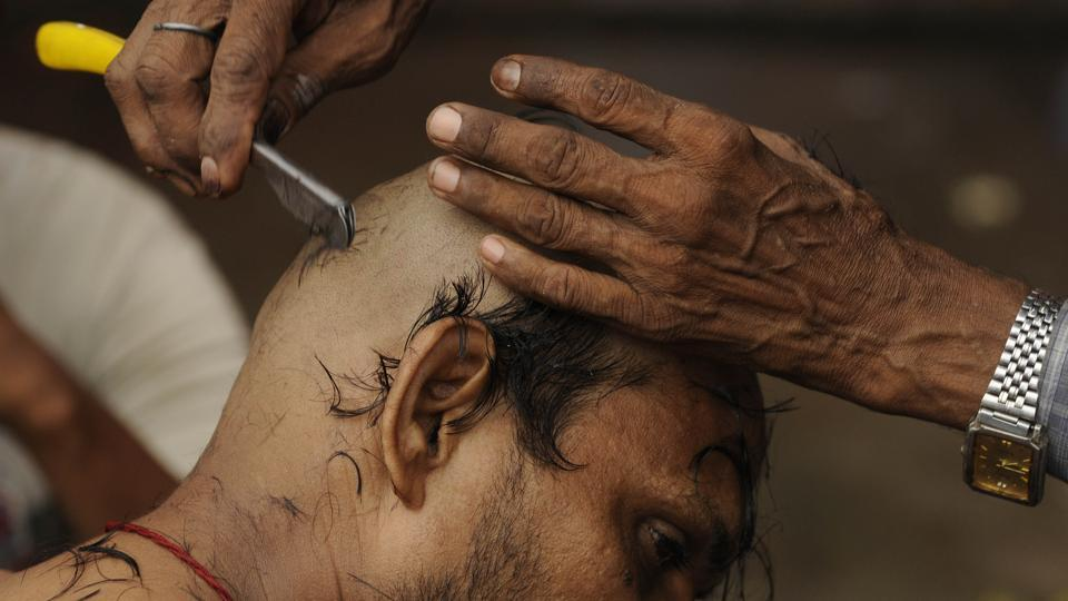 A man gets his head shaved in order as part of a Hindu ritual, which demands this of men who lose their fathers. The performance of 'Shraadh' by a son during Pitru Paksh is compulsory in Hinduism in order to make sure that the soul of the ancestor finds peace in heaven. (Samir Jana/HT PHOTO)