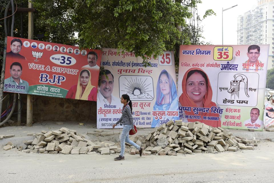 A girl walks past hoardings of MCG poll candidates on Tuesday.