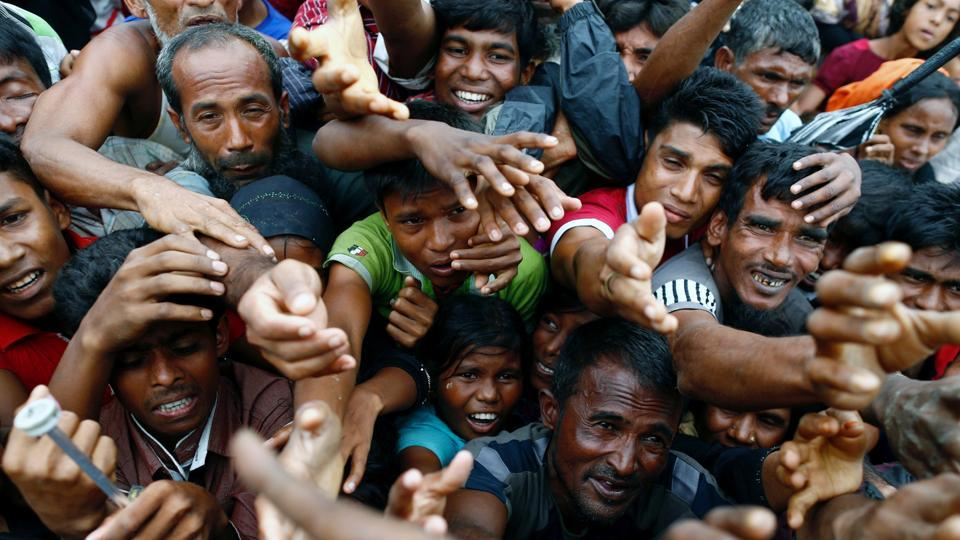 Rohingya refugees stretch their hands to receive aid distributed by local organisations at a makeshift camp in Cox's Bazar, Bangladesh.