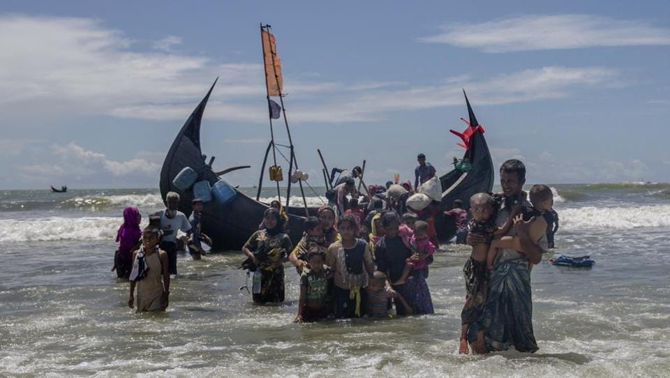 In this September 14, 2017 file photo, a Rohingya man carries two children to shore in Shah Porir Dwip, Bangladesh, after they arrived on a boat from Myanmar.