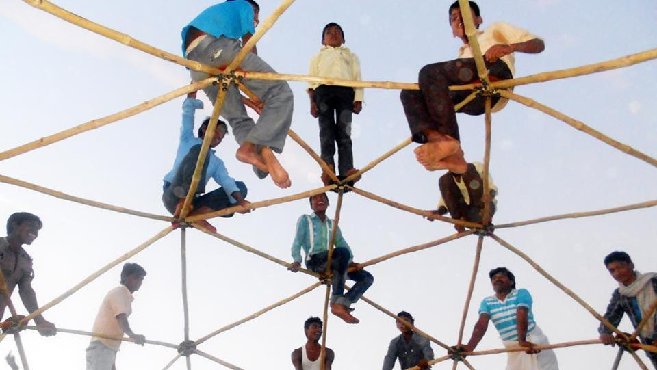 Tribals stand atop the roof of a bamboo dome to test its strength in Dharampuri village, Jhabua, Madhya Pradesh. This dome is used as an anganwadi building and is cost effective for the tribal economy. (HT Photo)