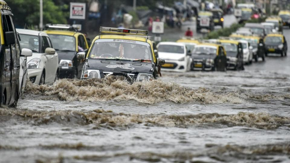 Cars pass through a waterlogged street in Wadala on Wednesday morning.