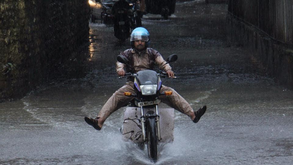 Widespread rain overnight left many parts of Mumbai waterlogged. A man rides through the waterlogged Malad Subway on Wednesday morning. (Pramod Thakur/hindustan times)
