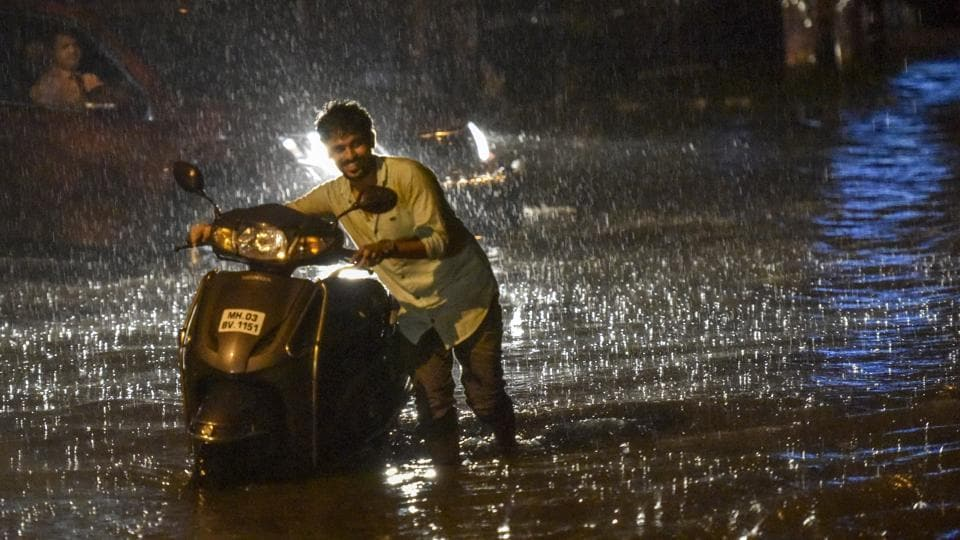 A man pushes his bike through a waterlogged street in Mumbai on Tuesday evening.