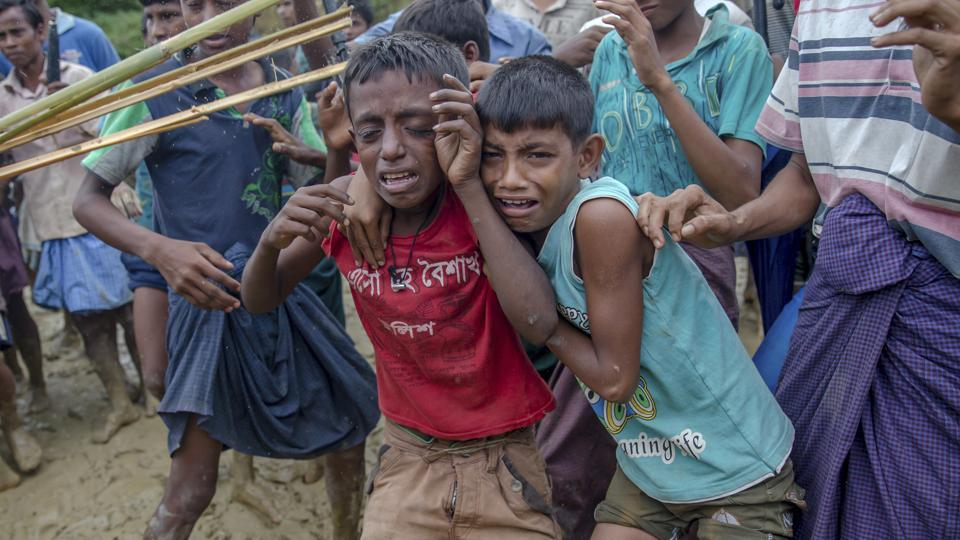 Rohingya Muslim boys, who crossed over from Myanmar into Bangladesh, cries as men push them away during distribution of food aid near Balukhali refugee camp, Bangladesh.