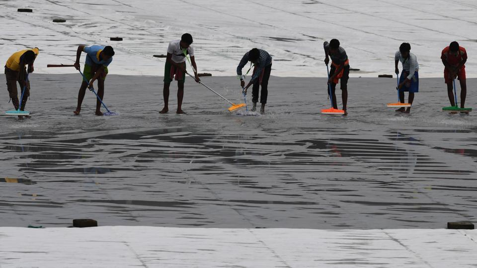 The ground staff worked hard to remove the excess water from the covers. (AFP)