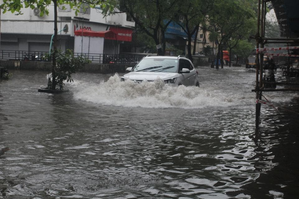 Vehicle move through a flooded road at Thane on Wednesday.