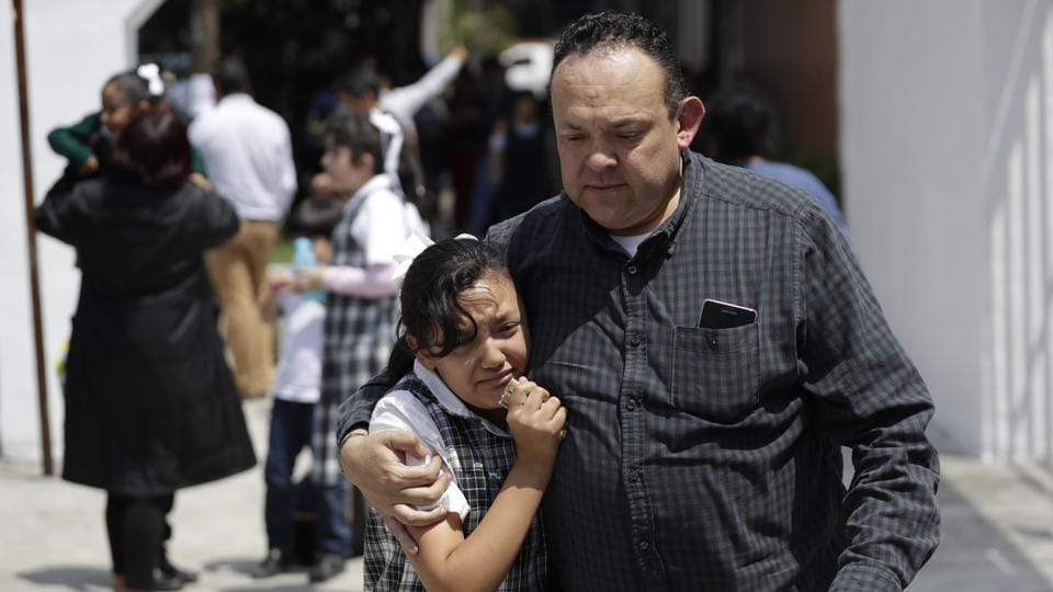 A man comforts a frightened student as he collects her from her school in the Roma neighborhood of Mexico City. Earthquakes of magnitude 7 or above are regarded as major and are capable of causing widespread heavy damage. Another 11 aftershocks were registered after the initial quake at around lunchtime on Tuesday, the most powerful of which measured 4.9, according to the USGS. (Rebecca Blackwell /  AP)