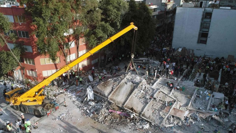 Rescuers with a crane look for survivors in a multistory building flattened by a powerful quake in Mexico City.