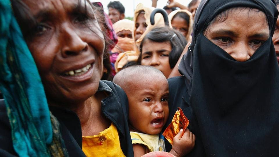 A Rohingya refugee baby cries as his mother jostles for aid in Cox's Bazar, Bangladesh.