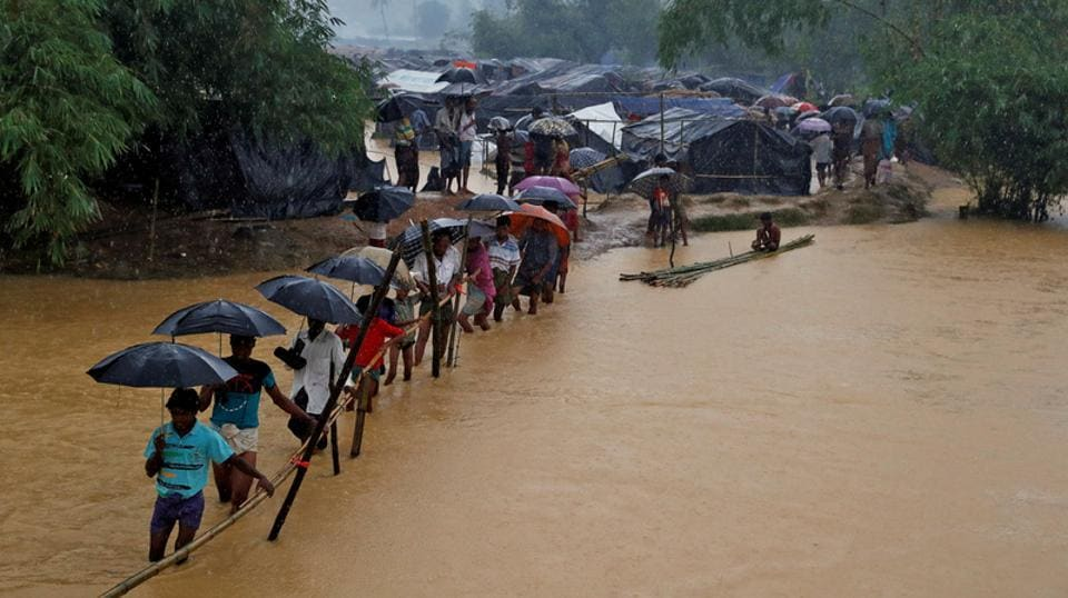 People cross a river from a Rohingya refugee camp in Cox's Bazar, Bangladesh. Myanmar State Counselor Aung San Suu Kyi has told ANI that she intended to not use 'emotive' terms for an already affected population.