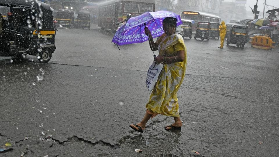 Five Western Railway trains have been cancelled. On Central Railways, six trains were cancelled and two diverted due to heavy rainfall. Here, people are seen traversing the rain in Andheri, Mumbai.  (Shashi S Kashyap / HT Photo)