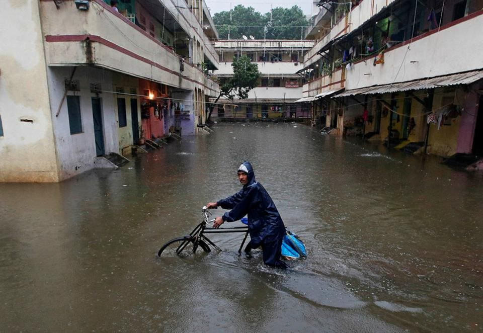 A delivery boy pushes his bicycle through a water-logged street after heavy rains at a residential colony in Mumbai. Massive waterlogging was reported in areas of Borivali, Sion, Hindmata in Dadar, Goregaon, Andheri, Kandivali, Malad, Kharghar, Mankhurd, and Bhandup. (Shailesh Andrade / Reuters)