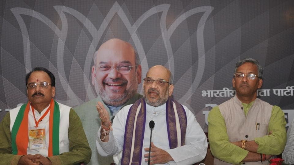 Flanked by BJP state head Ajay Bhatt and chief minister TS Rawat, BJP president Amit Shah addresses a press conference in Dehradun  on Wednesday.