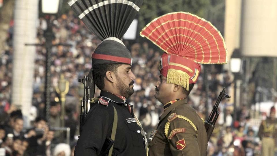 A Pakistani Ranger in black uniform and his Indian counterpart at the joint Pakistan-India border check post of Wagah near Lahore. AP photo