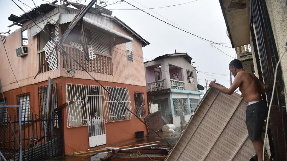 Residents of San Juan, Puerto Rico, deal with damages to their homes on September 20, 2017, as Hurricane Maria batters the island. Maria slammed into Puerto Rico on Wednesday, cutting power as terrified residents hunkered down in the face of the island's worst storm in living memory. After leaving a deadly trail of destruction on a string of smaller Caribbean islands, Maria made landfall on Puerto Rico's southeast coast around daybreak. (Hector  Retamal / AFP)