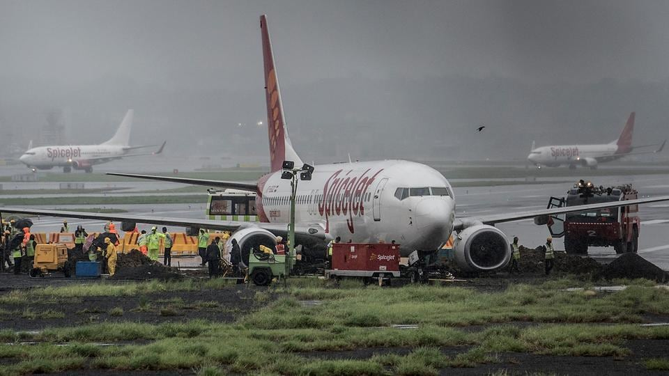 A Spice Jet aircraft overshot the wet main runway while landing and then got stuck in mud leading to suspension of flight operations on Tuesday.  (Satish Bate/HT Photo)