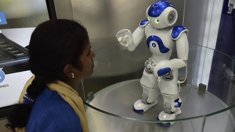 A staff of Canara Bank demonstrates Candi, the robot which welcomes customers as receptionists at Bengaluru Circle Office in Bengaluru, India, on Thursday, September 21, 2017.