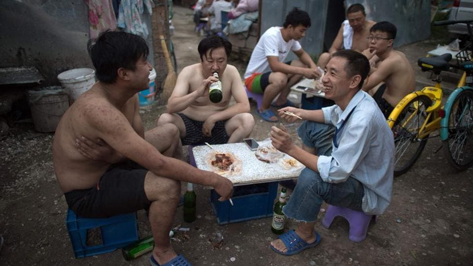 Surrounded by the sleek hi-tech campuses and luxury condominiums of 'Beijing's Silicon Valley', migrants from the countryside recreate village life, cooking in outdoor communal areas, playing cards and showering in the street. But their community's days are numbered. (Nicolas Asfouri / AFP)
